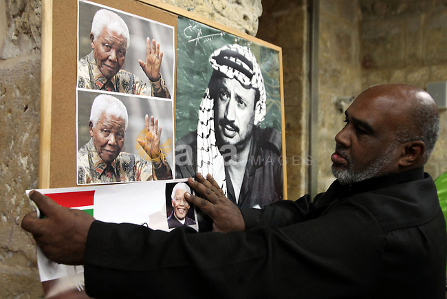 Palestinians gather at a candle memorial for late South African President Nelson Mandela in an area of Jerusalem's Old City popular to Africans, 07 December 2013. Nobel Peace Prize winner Nelson Mandela died at age 95, in Johannesburg, South Africa, on 05 December 2013. A former lawyer, Mandela was the first black President of South Africa voted into power after the countries first free and fair democratic elections that witnessed the end of the Apartheid system in 1994. Mandela was founding member of the ANC (African National Congress) and anti-apartheid activist who served 27 years in prison, spending many of these years on Robben Island. In South Africa, Mandela is often known as Tata Madiba, an honorary title adopted by elders of Mandela's clan. Mandela won the Nobel Peace Prize in 1993.  Photo by Saeed Qaq