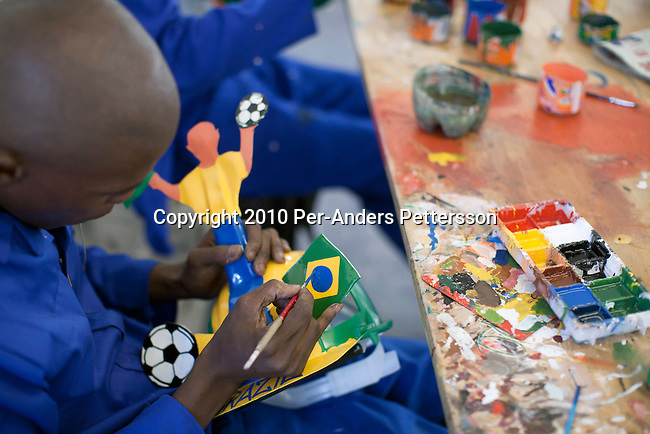 JOHANNESBURG, SOUTH AFRICA - MAY 10: An unidentified artist paints a Brazilian flag on a Makarapa helmet on May 10, 2010, in Alfred Baloyi's studio in Wynberg, north of Johannesburg, South Africa. Mr. Baloyi, and a diehard Kaizer Chiefs soccer fan, started to make these hats in 1979. Initially he asked a friend who worked at a construction site for a helmet, as he wanted to protect himself from missiles at games. He later started to paint it, and later started to make this different figures hand cut out from the helmet. During the years he has made many different artistic hats that are on display in his studio in a shack in Primrose, Johannesburg. He later gave up his job as a washer of busses. From his small workshop in a squatter camp in Primrose south east of Johannesburg he recently made partner with an investor and have a brand new factory with about fifty people employed to make the hats. (Photo by Per-Anders Pettersson/Getty Images)