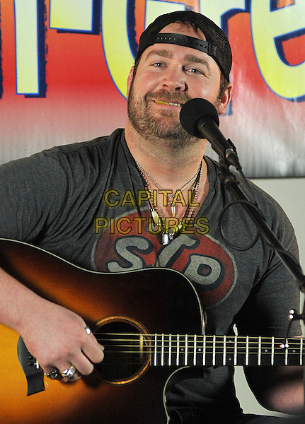 "LEE BRICE.National Country Music artist Lee Brice stops by ""Pittsburgh's Best Country"" Y108 Radio Station to chat and perform a live acoustic set, Pittsburgh, PA, USA..March 9th, 2011               .stage concert live gig performance music half length grey gray t-shirt sitting baseball cap hat backwards guitar stubble facial hair singing               .CAP/ADM/JN.©Jason L Nelson/AdMedia/Capital Pictures."