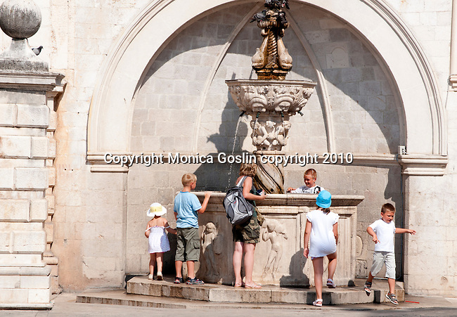 Kids gather around the Small Onofrio's Fountain on a hot summer day in Dubrovnik, Croatia.