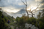 The misty mountains and landscape of Corsica are the backdrop for a woman hiking along the path.