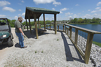 NWA Democrat-Gazette/FLIP PUTTHOFF <br />OUT WITH PAVILION WEEDS<br />Harold Clark with the Arkansas Game and Fish Commission sprays weeds Tuesday April 18 2017 at the Charile Craig State Fish Hatchery wildlife viewing area in Centerton. The viewing pavilion and hatchery grounds are a haven for bird watchers all year. Signs at the pavilion help visitors identify birds commonly seen at the fish hatchery.