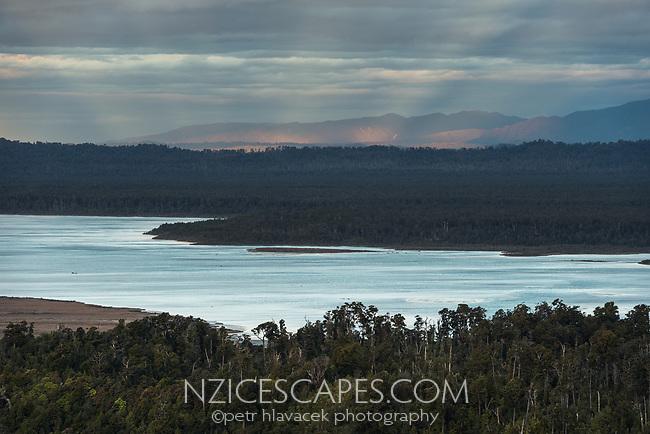 Sunset over Okarito Lagoon with beams of setting sun, Westland Tai Poutini National Park, West Coast, South Westland, UNESCO World Heritage Area, New Zealand, NZ