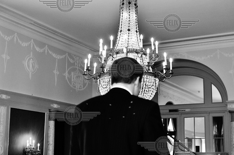 A man walks past a huge chandelier during the annual press conference of the Swiss Private Bankers Association, held in the luxury Bellevue Palace Hotel. .. /Felix Features