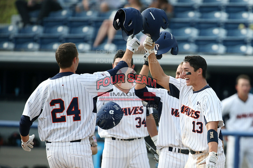 Matt Gelalich (13) of the Pepperdine Waves greets his teammate Brad Anderson (24) after Anderson's home run during a game against the Texas A&M Aggies at Eddy D. Field Stadium on February 26, 2016 in Malibu, California. Pepperdine defeated Texas A&M, 7-5. (Larry Goren/Four Seam Images)