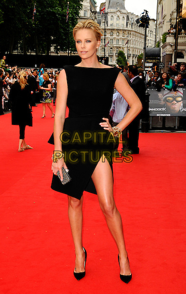 """CHARLIZE THERON.Attending the UK Gala Premiere of """"Hancock"""" held at the Vue West End, Leicester Square, London, England. .June 18th 2008.full length black dress slit split heels gold bracelets silver clutch bag hand on hip .CAP/CAN.©Can Nguyen/Capital Pictures."""