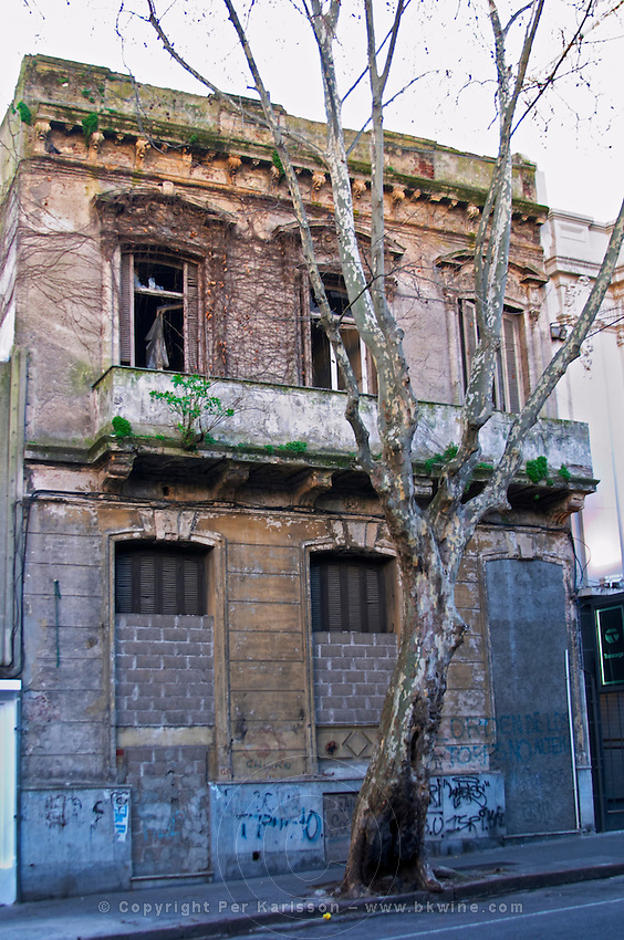 An old run down ruin of a town house building in the city, doors and windows shut with bricks and mortar. Montevideo, Uruguay, South America