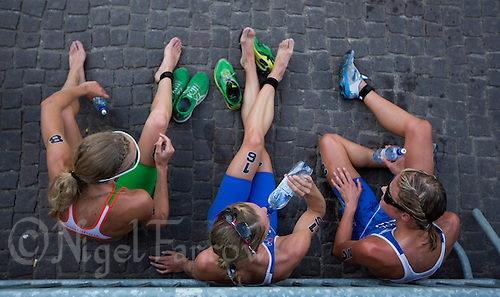 24 AUG 2013 - STOCKHOLM, SWE - Aileen Reid (IRL) (left) of Ireland, and Katie  Hewison (GBR) (centre) and Vanessa Raw (GBR) (right), both of Great Britain, recover after finishing the elite women's ITU 2013 World Triathlon Series round in Gamla Stan in Stockholm, Sweden (PHOTO COPYRIGHT © 2013 NIGEL FARROW, ALL RIGHTS RESERVED)