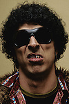 Close up of a man with metal teeth, sunglasses and curly black hair