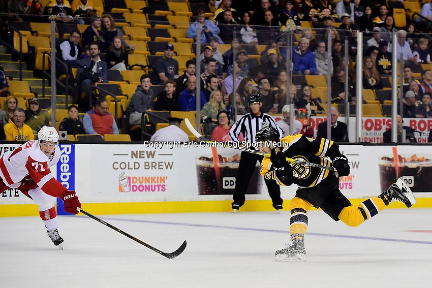 Wednesday, September 28, 2016: Boston Bruins defenseman Colin Miller (48) shots the puck as Detroit Red Wings center Dylan Larkin (71) defends the play during the NHL game between the Detroit Red Wings and the Boston Bruins held at TD Garden, in Boston, Massachusetts. Eric Canha/CSM