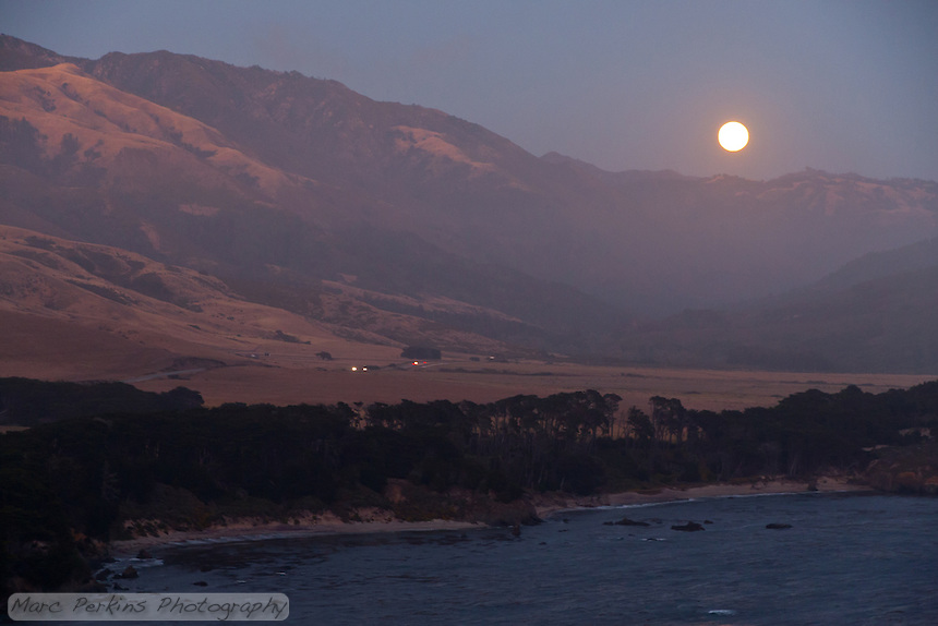 The full moon rises over California Highway 1 with the Pacific Ocean in the foreground.  Seen from the Point Sur Light Station on one of their moonrise tours.
