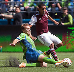 Seattle Sounders' Dylan Remick, left, kicks the ball away from Colorado Rapids' Gabriel Torres during an MLS match on April 26, 2014 in Seattle, Washington.  The Seattle Sounders beat the Colorado Rapids 4-1.  Jim Bryant Photo. ©2014. All Rights Reserved.