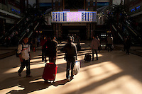 Daytime landscape view of people looking at the train schedule in the B?ij?ng Zhàn in D?ngchéng Q? in Beijing.  © LAN