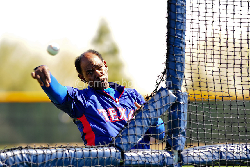 Feb 24, 2011; Surprise, AZ, USA; Texas Rangers manager Ron Washington throws batting practice from behind a fence during a full team workout at the Surprise Recreation Campus.