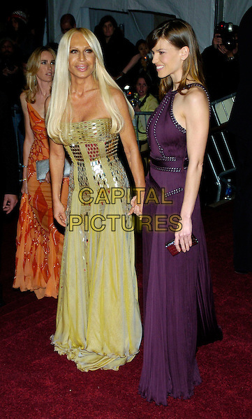 "DONATELLA VERSACE & HILARY SWANK.2007 Metropolitan Museum of Art Costume Institute Gala celebrating ""Poiret: King of Fashion"" exibition at the Metropolitan Museum of Art, New York City, New York, USA..May 7th, 2007.full length gold metallic dress yellow purple strapless clutch purse profile .CAP/ADM/BL.©Bill Lyons/AdMedia/Capital Pictures *** Local Caption ***"