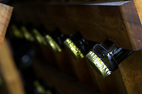 Bottles of sparkling wine aging upside down in pupitres. detail of a crown cork beer bottle capsule Bodega Del Anelo Winery, also called Finca Roja, Anelo Region, Neuquen, Patagonia, Argentina, South America