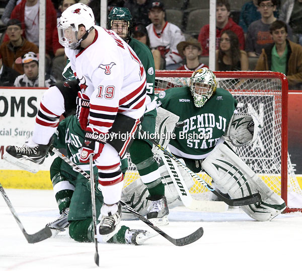 University of Nebraska Omaha's Ryan Walters leaps as a teammate fires a shot on Bemidji State goalie Dan Bakala through traffic during the third period. Bemidji State beat UNO 4-2 Friday night during the first round of the WCHA playoffs at Qwest Center Omaha. (Photo by Michelle Bishop)