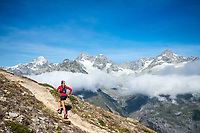 A woman trail running above Zermatt, Switzerland with views of the 4000 meter peaks above town.