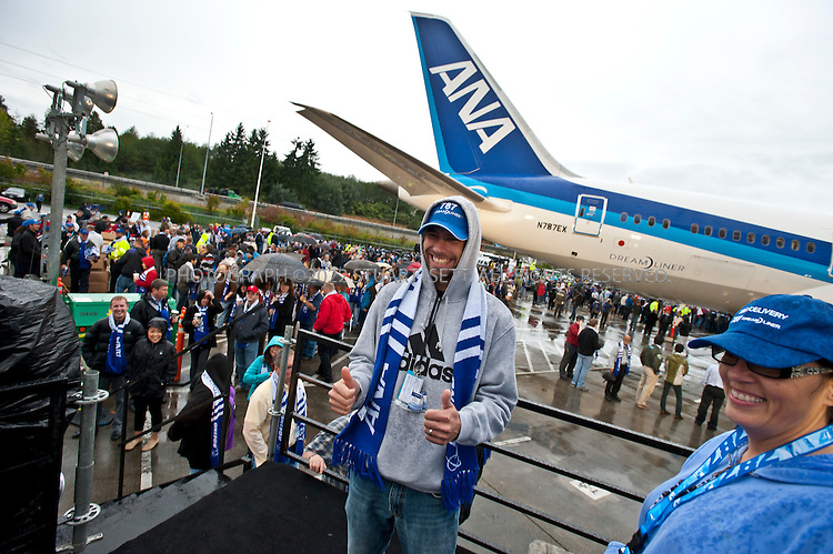 9/26/2011--Everett, WA, USA..Boeing employee Try Schuh poses for a photo in front of a Beong 787 Dreamliner...Thousands of Boeing employees gathered in the rain to celebrate the delivery of the first 787 Dreamliner to launch customer ANA (All Nippon Airways) from Japan. The fuel efficient composite aircraft was towed to the front of the huge factory doors where it was assembled, and presented to ANA President Shinichiro Ito in front of thousands of invited dignitaries and Boeing workers. The first 787 was supposed to be delivered 3 years ago but despite delays Boeing still has orders for over 800 of the planes...©2011 Stuart Isett. All rights reserved.