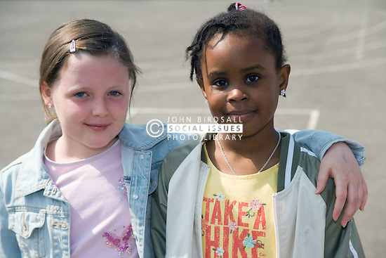 Two girls standing together in school playground,