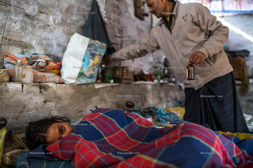 Meera lies in bed as her father brings medication to her in their shelter where the family live and work as earring makers in Varanasi, Uttar Pradesh, India on 19 November 2013.