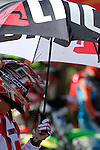 A rider catches shade under an umbrella before the start while on the course at the Unadilla Valley Sports Center in New Berlin, New York on July 16, 2006, during the AMA Toyota Motocross Championship.