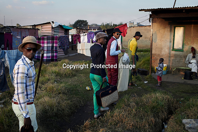 SOWETO, SOUTH AFRICA MAY 21: Models walk to a location for the group Smarteez during a photo shoot on May 21, 2013 in Kliptown section of Soweto, South Africa. They did a photo shoot together with a new collection. Soweto today is a mix of old housing and newly constructed townhouses. A new hungry black middle-class is growing steadily. Many residents work in Johannesburg but the last years many shopping malls have been built, and people are starting to spend their money in Soweto. (Photo by: Per-Anders Pettersson)
