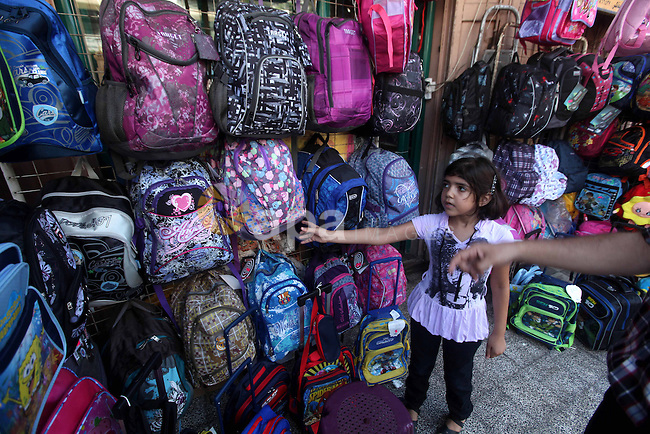 A Palestinian girl looks at school bags displayed at a market in Gaza city on Aug 28, 2012. Next Sunday the First day for the new school year according to Palestinian Ministry of Education in the Gaza strip and the West Bank. Photo by Majdi Fathi