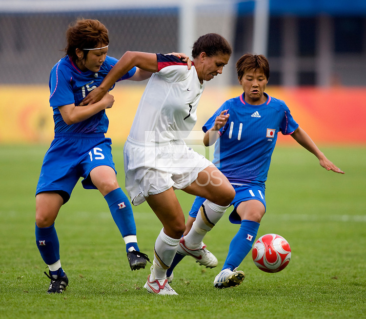 USWNT midfielder (7) Shannon Boxx fights for the ball with Japanese midfielders (15) Mizuho Sakaguchi and (11) Shinobu Ohnowhile playing at Qinhuangdao Stadium. The US defeated Japan, 1-0, during first round play at the 2008 Beijing Olympics in Qinhuangdao, China.