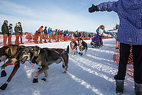 Angie Taggart gives high-fives to spectators as she runs down the chute leaving the restart of the Iditarod sled dog race at Willow, Alaska  Sunday, March 3, 2013.