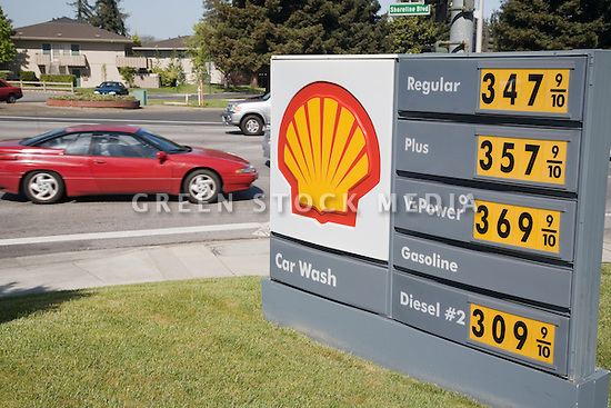 A red car drives by a Shell gas station sign showing gas prices way over three dollars a gallon. Mountain View, California, April 24, 2007.