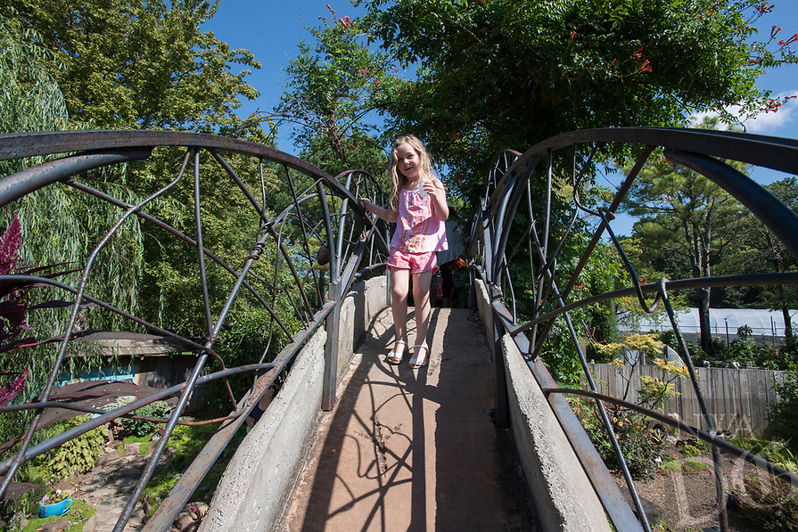 NWA Democrat-Gazette/J.T. WAMPLER Anna Mooneyham, 5, of Fayetteville walks across a bridge in the children's garden Wednesday July 12, 2017 at the Botanical Garden of the Ozarks. Little Sprouts is a weekly botanically-themed program for preschoolers at the garden.