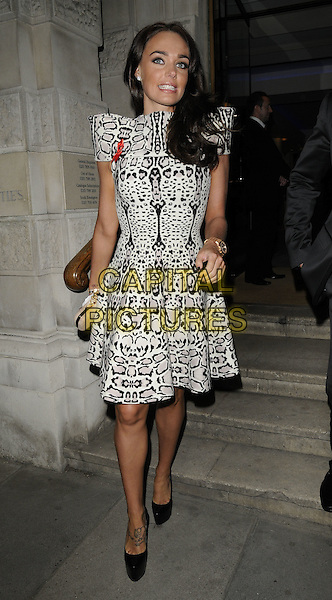 TAMARA ECCLESTONE .The Lighthouse Gala Auction, Christie's, London, England, UK, March 21st 2011..full length black and cream print shoulder pads heart ribbon red brooch pin hands on hips dress platform shoes tattoo animal leopard white .CAP/CAN.©Can Nguyen/Capital Pictures.