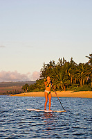 Young woman standup paddling (SUP) at sunset off the shores of Mokuleia