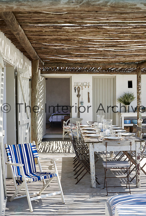 A wooden table, laid for lunch, and chairs are set out on a covered terrace in the sunshine.