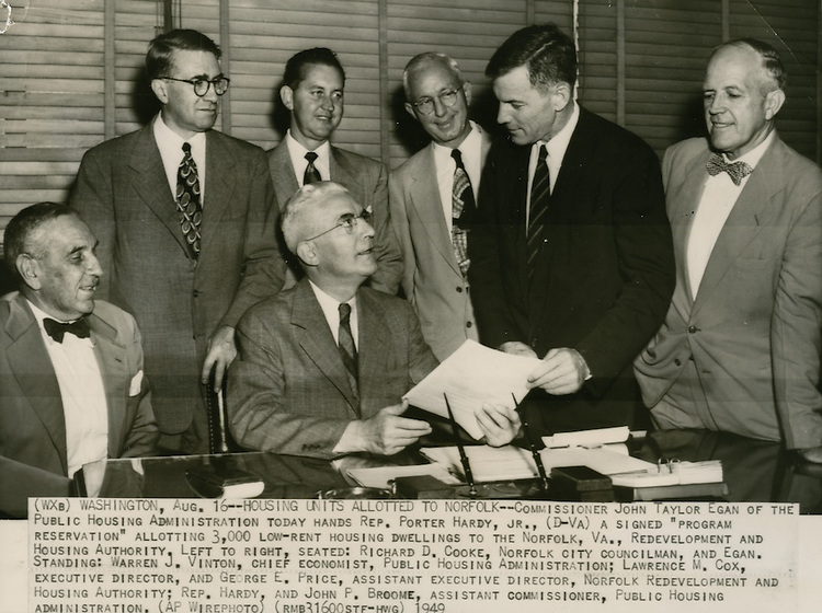 "1949 August 16..Historical..WASHINGTON - HOUSING UNITS ALLOTTED TO NORFOLK--Commissioner John Taylor Egan of the Public Housing Administration today hands Rep. Porter Hardy, Jr. (D-VA) a signed ""Program Reservation"" allotting 3000 low-rent housing dwellings to the Norfolk VA Redevelopment & Housing Authority..Left to right-  .Seated: Richard D. Cooke, Norfolk City Councilman, and Egan..Standing:  Warren J. Vinton, Chief Economist, PHA, Lawrence M. Cox, Executive Director, & George E. Price, Assistant Executive Director, NRHA; Rep. Hardy and John P. Broome, Assistant Commissioner, PHA (AP Wirephoto) (RMB31600STF-HWG)...NEG#.NRHA# 775.."