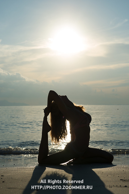 Girl's silhoutte behind Andaman sea and sun, practicing beach yoga at sunrise in Thailand
