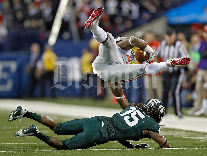 Ohio State Buckeyes running back Carlos Hyde (34) gets dropped in the backfield by Michigan State Spartans cornerback Trae Waynes (15) in the 1st quarter during the Big 10 Championship game at Lucas Oil Stadium in Indianapolis, Ind on December 7, 2013.  (Dispatch photo by Kyle Robertson)