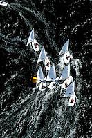 """Kieler Woche:EUROPA, DEUTSCHLAND, SCHLESWIG- HOLSTEIN 22.06.2005:Kieler Woche, Segler der Laser Klasse im Gedraenge an der Wende. ..Der Laser ist eine 4,23 m lange, 1,37 m breite und 57 kg (Rumpf) schwere Einmann-Jolle mit einem Segel...Der Laser wurde 1970 vom Amerikaner Bruce Kirby als Einhand-Jolle entworfen. Primaere Zielsetzung war damals ein Boot für die Freizeit zu entwerfen, deshalb auch der ursprüngliche Name """"Freetime""""..Seine einfache Bauweise und niedrige Anschaffungskosten führten zu einer raschen Ausbreitung. Ende des Jahres 2004 gab es ca. 180.000 Boote auf der Welt!.Der Laser ist eine One-Design Bootsklasse und wird von der Firma Performance Sailcraft Ltd. in England gefertigt. Weiterhin gibt es Lizenznehmer in Australien und in Chile..Das Niveau in der Laser-Klasse gilt als eines der höchsten der olympischen Bootsklassen..Luftaufnahme, Luftbild,  Luftansicht."""