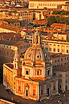 Looking down at the streets around the Altare della Patria at sunset with a detailed view of the 16th century Santa Maria di Loreto
