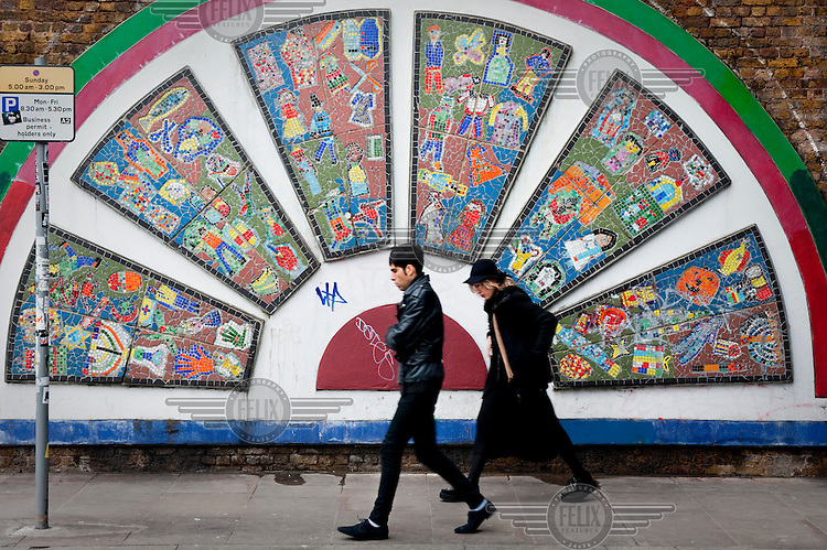 People walk past a mosaic mural on Brick Lane in Shoreditch, London.