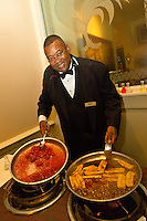 Waiter with desserts (Crepes Fitzgerald on left and Bananas Foster on right) that he has just cooked, Brennan's Restaurant in the French Quarter, New Orleans, Louisiana, USA