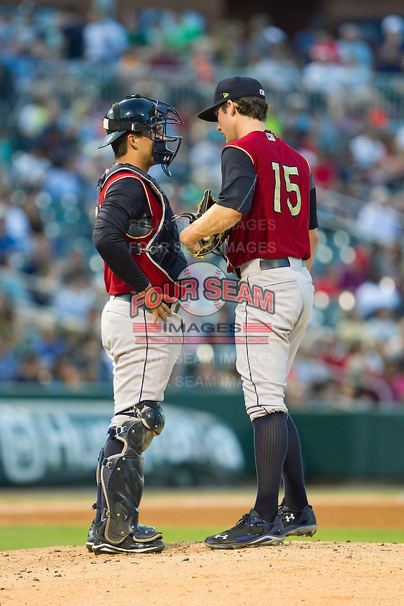 Scranton/Wilkes-Barre RailRiders catcher John Ryan Murphy (34) has a chat on the mound with starting pitcher Bryan Mitchell (15) during the game against the Charlotte Knights at BB&T Ballpark on July 17, 2014 in Charlotte, North Carolina.  The Knights defeated the RailRiders 9-5.  (Brian Westerholt/Four Seam Images)