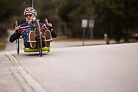 Morehead City, NC -- Quadriplegic hand cyclist Paul Kelly, 62, climbs a hill on Oakleaf Drive as he trains for the Boston Marathon Tuesday, March 27, 2018. (Justin Cook for The Wall Street Journal)<br /> <br /> SUMMARY:<br /> <br /> Paul Kelly, hand cyclist, Beaufort, NC Training for the Boston Marathon so we would want to shoot in March to run the week before the marathon or marathon Monday, Apriln16. Life as a quadriplegic doesn't keep 62-year-old Paul Kelly on the sidelines. After breaking his neck in a swimming accident in 1978, Kelly was determined to find fitness activities to maintain an active lifestyle. He discovered handcycles while watching his niece compete in the 2006 Marine Corps Marathon and was inspired to start his own marathon career to stay fit. Paul has competed in over 100 half and full marathons. On April 16, he will celebrate his 40th year of living as a quadriplegic by taking on one of the most coveted races for a marathoner -- the Boston Marathon. Kelly is among the 60 handcyclists competing in the 2018 Boston Marathon with a qualifying time of 1:26:37. Most of Paul's distance training takes place at Bogue Banks, which includes Atlantic Beach, Salter Path, and Emerald Isle, N.C. It's Nicholas Sparks worthy scenery with its marshes, waterways, inlets and small islands. Paul is particularly fond of the approach from Atlantic Beach to Bogue Banks -- it's via the high-rise bridge. In cold weather, Paul has to be mindful of the environment and dress in a manner that insulates his legs while also allowing his upper body to ventilate. Paul chooses to train at times of day when the temperatures are more reasonable. He uses hand warmers in his gloves, on the inside the grips on his handcycle and in the legs of his trousers.