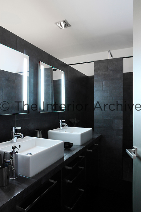 The walls of the bathroom have been faced with dark grey slate tiles and a shower is situated behind a slate partition at one end