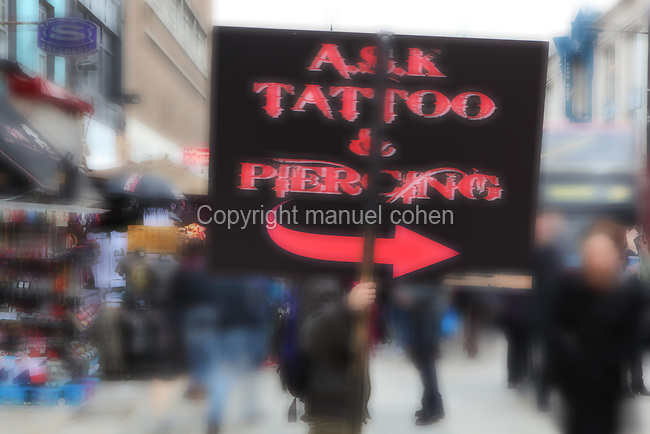 High Street, Camden Town atmosphere, focussed view of a Tattoo and Piercing red advert held by a young man with the crowd and shops in the background, London, UK. Picture by Manuel Cohen