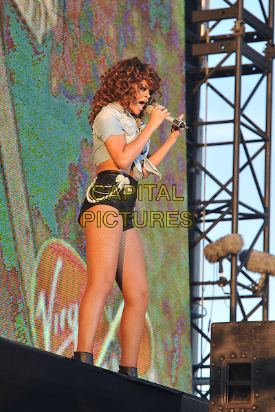 Rihanna (Robyn Rihanna Fenty).Rihanna performs at Day Two V Festival at Hylands Park, Chelmsford, Essex, England..August 21st, 2011.stage concert live gig performance music full length denim knotted shirt singing profile belly stomach midriff micro shorts black pearls brooch fishnet stockings .CAP/MAR.© Martin Harris/Capital Pictures.