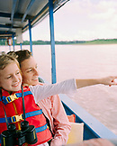 PERU, Amazon Rainforest, South America, Latin America, smiling mother and daughter travelling in boat along the Tambopata River.