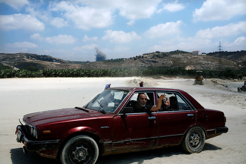 South Lebanon, July 21, 2006.Ten of thousands of refugees leave their homes and villages under the israeli bombardment to try and reach a relative safety in Beirut, in the montains or for the priviledged, abroad. As this family drives through a dirt road to bypass a destroyed bridge on the main road, a large Israeli bomb explodes about a mile away.