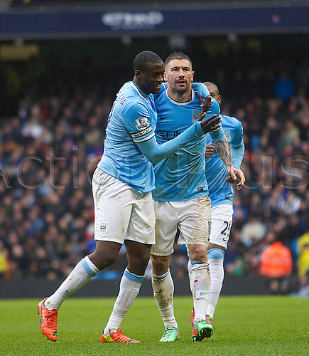 22.03.2014  Manchester, England. Yaya Toure of Manchester City scores to make it 3-0 and celebrates with team mate Aleksandar Kolarov  during the Premier League game between Manchester City and Fulham from the Etihad Stadium.